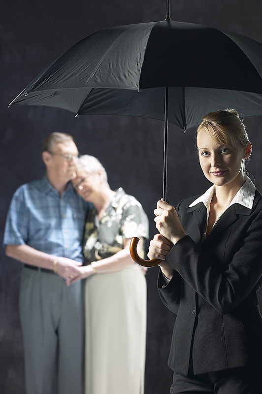 Woman with umbrella - elderly couple in background